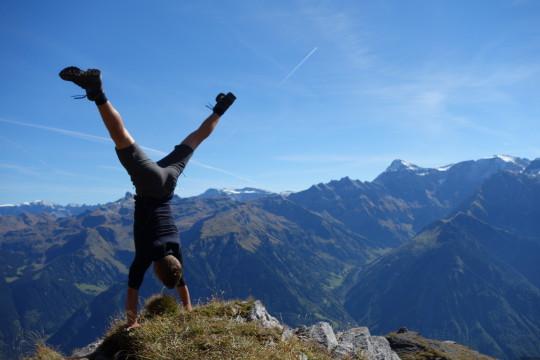 Une personne effectue un appui renversé au sommet d'une montagne.