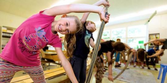 Foto: in primo piano una bambina tiene una corda con entrambe le mani sopra la testa e si china di lato
