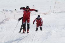 Trois skieurs passent par-dessus une bosse sur un parcours.