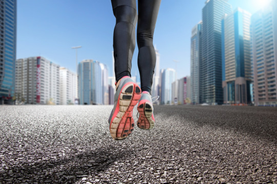 Gros plan sur les jambes d'une personnes faisant un jogging dans une ville.