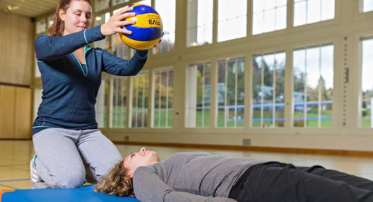 Una ragazza è stesa per terra in una palestra e un'altra tiene un pallone in mano sopra il suo viso