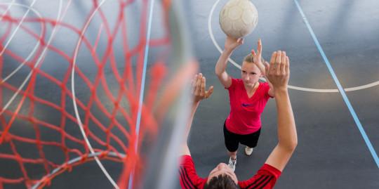 Foto: Spielerin versucht einen Korbwurf während ein Spieler verteidigt.
