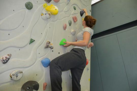 Junge Frau klettert eine Wand hoch.