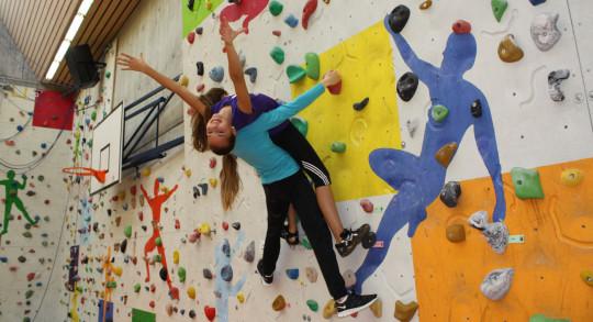Foto: Zwei Schülerinnen hängen in der Kletterwand, eine lehnt sich an die andere.