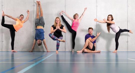 Mehrere Personen in unterschiedlichen Yoga-Stellungen vor einer Mauer in der Sporthalle.