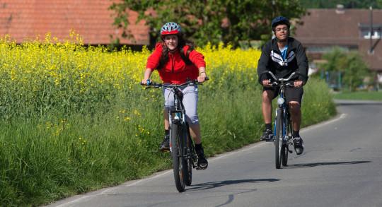 Zwei Jugendliche auf dem Fahrrad auf wenig befahrener Strasse.