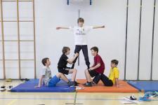 Fünf Schüler machen eine Pyramide.