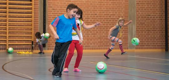 Dei bambini giocano con diversi palloni da calcio in una palestra.