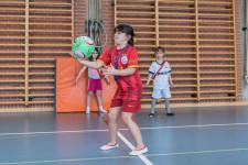 Mädchen fasst den Ball mit der Hand an.