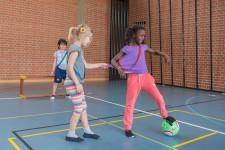 Ein Mädchen schirmt den Ball gegen eine Gegenspieler ab, die sie am T-Shirt zupft.