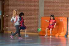 Drei Kinder beim Fussballspiel auf eine Matte.