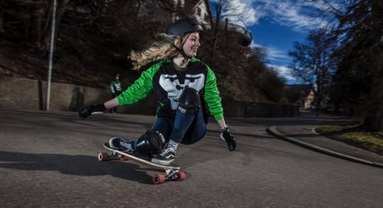 Foto: una ragazza esegue una curva su un longboard skate