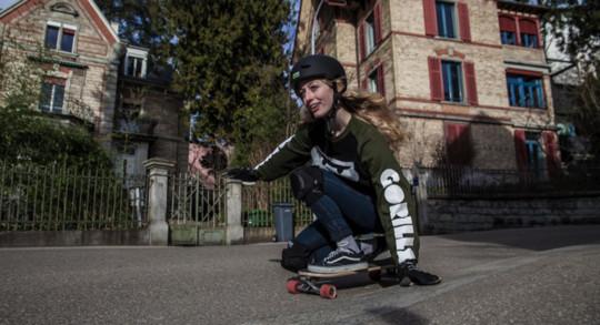 Un femme roule en skate sur une route de quartier.