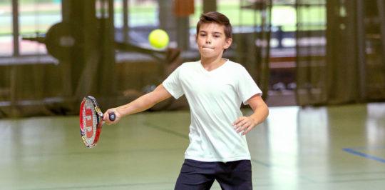 Foto: Knabe bei Ballabnhame mit Tennisschläger.