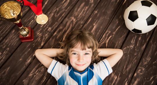 Lächelndes Mädchen liegt zufrieden am Boden zwischen Pokal, Medaille und Fussball.
