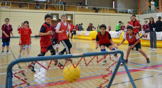 Des enfants sont en position de défense pour attraper le ballon.