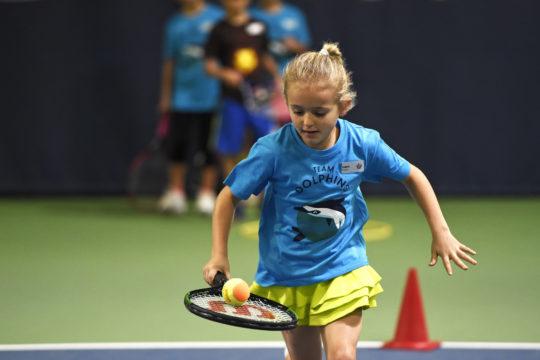 Una bambina corre trasportando una pallina su una racchetta