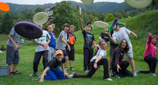 Mehrere Jugendliche werfen mehrere Frisbee-Scheiben.
