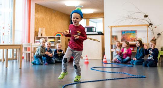 Foto: Kind rennt einem Seil entlang und wird von anderen angespornt.