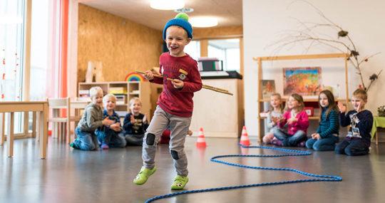 Foto: un bambino corre lungo una corda indossando un berretto invernale in un'aula di una scuola dell'infanzia