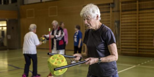 Foto: Reife Dame beim Balancieren eines Schaumstoffwürfels mit zwei Stäben.