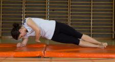 Une jeune fem effectue un exercice de renforcement des muscles latéraux du tronc.