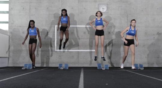Quatre jeunes athlètes au départ d'un sprint.