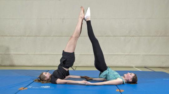 Deux jeunes filles effectuent un appui renversé sur les épaules.