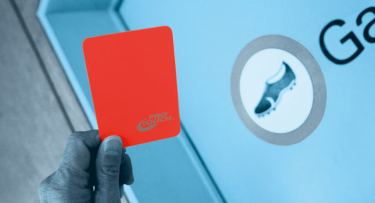 Hand zeigt rote Karte, im Hintergrund eine Garderobentüre.