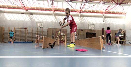 Junge spielt Minigolf in der Turnhalle, mit dort vorhandenem Material.