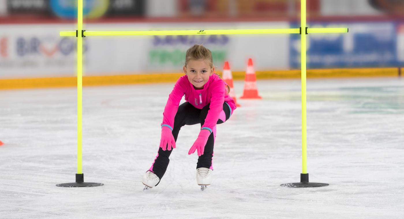 Une jeune fille patine par-dessous une barre.