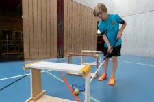Foto: Schüler spielt durch Schwedenkastenelemente einen Tennisball mit Unihockeyschläger.
