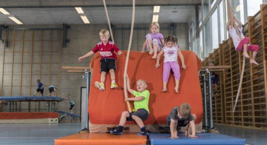 Foto: Verschiedene Kinder rutschen, springen, hangeln sich von einem Mattenberg auf Bodenmatten.