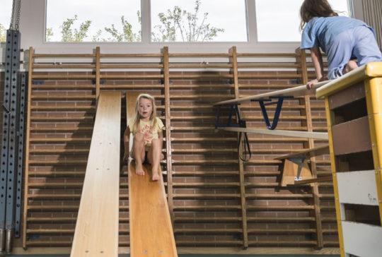 Foto: Ein Kind rutscht vorsichtig eine Langbank hinunter, die schräg an der Sprossenwand befestigt ist.