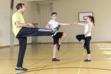 Lehrperson zeigt zwei Jugendlichen einen Rock'n'Roll-Schritt.