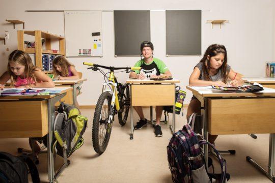 Biker und Schülerinnen im Schulziummer am Arbeiten