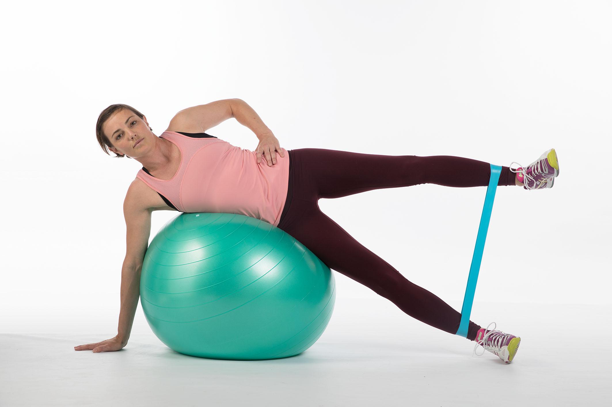 Foto: Eine junge Frau liegt seitwärts über einen Swissball, mit einem Miniband um die Knöchel