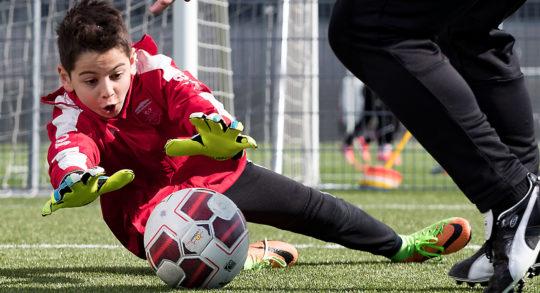 Un jeune gardien s'apprête à bloquer le ballon dans les pieds d'un joueur.