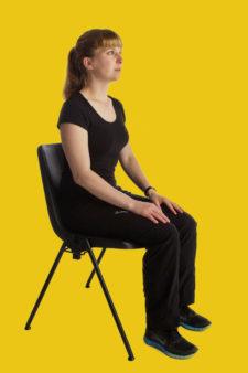 Frau sitzt auf Stuhl und entspannt sich.
