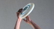 Hände, die einen Frisbee fangen.