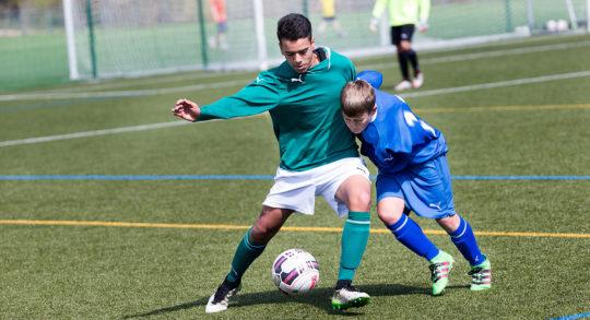 Due ragazzi di taglie diverse si contendono un pallone durante una partita di calcio