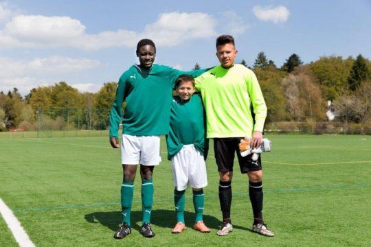 Foto: Drei Nachwuchsfussballer mit markantem Grössenunterschied.