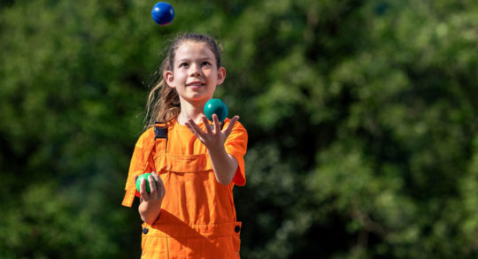 Foto: Ein Mädchen jongliert mit drei farbigen Bällen