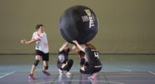 Un joueur s'appête à frapper le ballon tenus par trois coéquipiers.