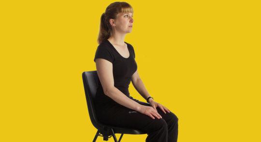 Una ragazza seduta su una sedia da ufficio in posizione di rilassamento