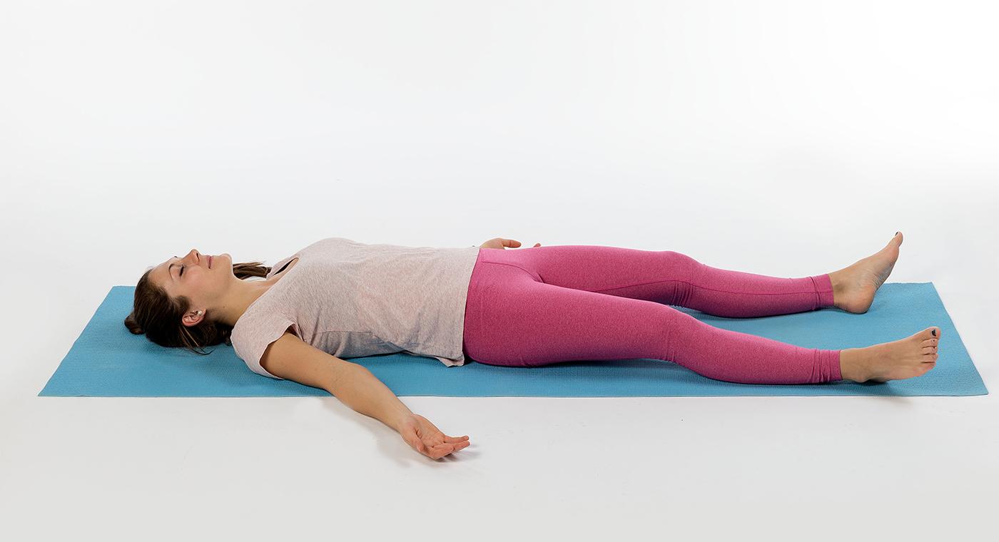 Una ragazza è sdraiata su un tappetino da yoga con gli occhi chiusi