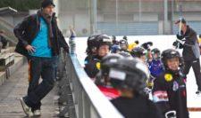 Un genitore osserva l'allenamento di hockey di una squadra di pulcini