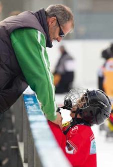 Photo: Un père souriant encourage son hockeyeur de fils.