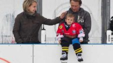 Foto: due genitori di un piccolo giocatore di hockey si occupano amorevolmente del figlio