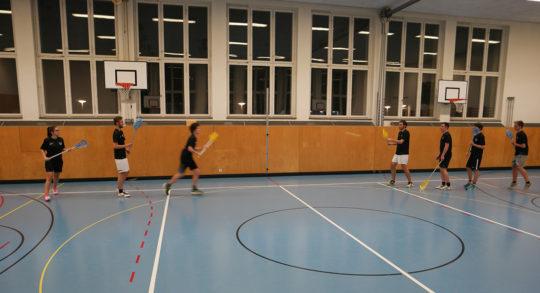 Foto: due squadre impegnate a giocare a intercrosse in una palestra